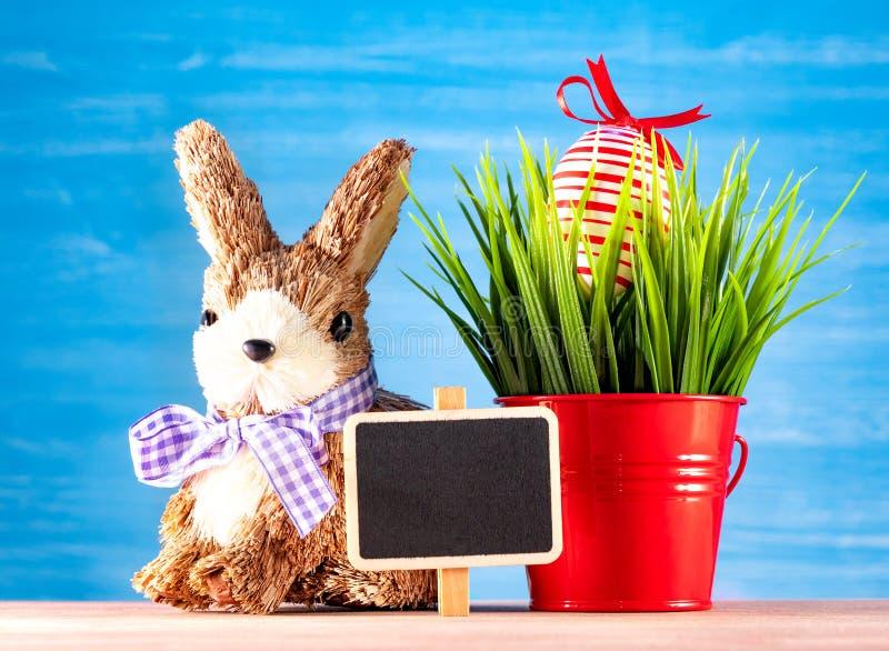复活节彩蛋和逗人喜爱的兔宝宝在木桌上与绿草 欢乐的装饰 免版税库存图片