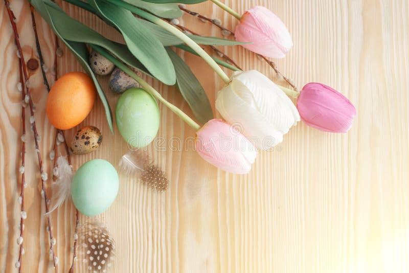 复活节彩蛋和郁金香在一张木桌上 r 免版税库存照片