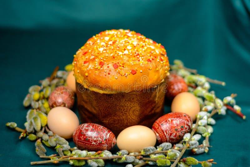 复活节彩蛋和面包在黑暗的背景有杨柳分支背景 库存照片