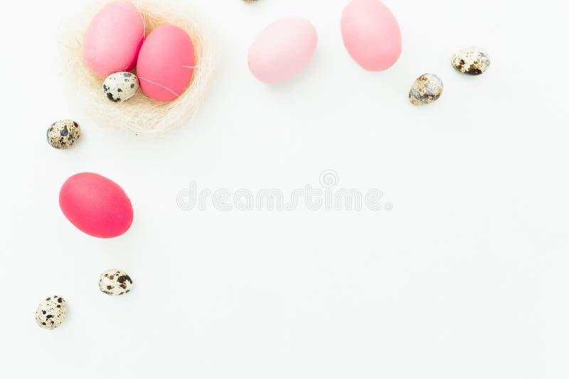 复活节彩蛋和鹌鹑蛋在巢在白色背景,顶视图,油脂位置 与拷贝空间的复活节欢乐概念 免版税库存照片