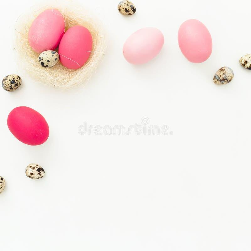 复活节彩蛋和鹌鹑蛋在巢在白色背景,顶视图,油脂位置 复活节假日概念 库存照片