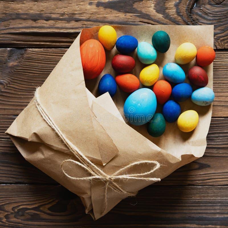 复活节彩蛋在一个纸袋被包装作为在木背景的一件礼物 免版税库存照片