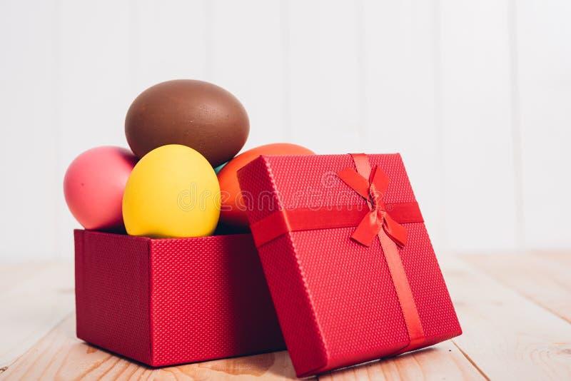 复活节彩蛋在木背景的红色箱子礼物清洗 库存图片