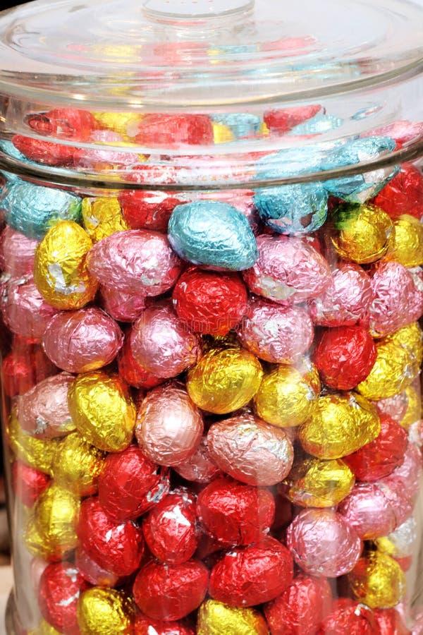复活节彩蛋在糖果玻璃瓶子多色背景中 库存照片