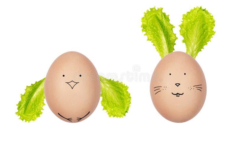 复活节彩蛋用新鲜的沙拉叶子装饰了 在鸡蛋画的滑稽的面孔 复活节兔子和鸡由hen's鸡蛋制成 库存照片