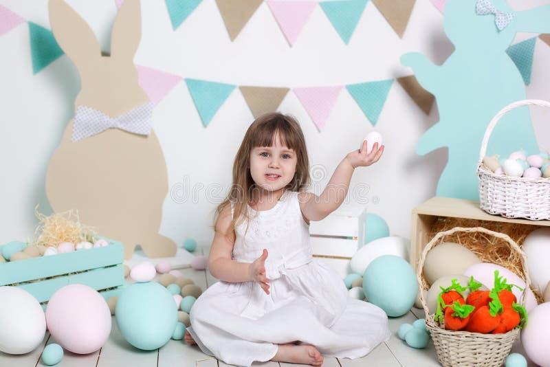 复活节快乐!一件白色礼服的一美丽的女孩在一处明亮的风景附近坐并且拿着复活节彩蛋 复活节兔子和红萝卜 库存照片