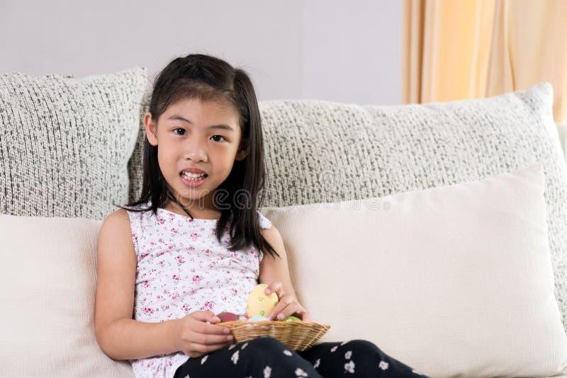 复活节快乐!两个逗人喜爱的小孩坐沙发用在巢或篮子的复活节彩蛋 免版税库存图片