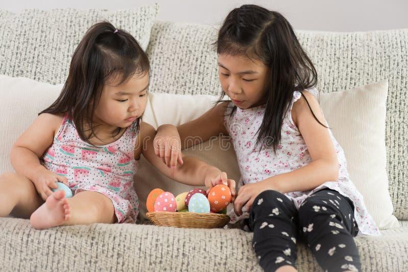 复活节快乐!两个逗人喜爱的小孩坐沙发用在巢或篮子的复活节彩蛋 库存图片