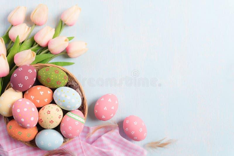 复活节快乐!五颜六色在巢与桃红色郁金香和羽毛的复活节彩蛋在天空蔚蓝木背景 库存图片