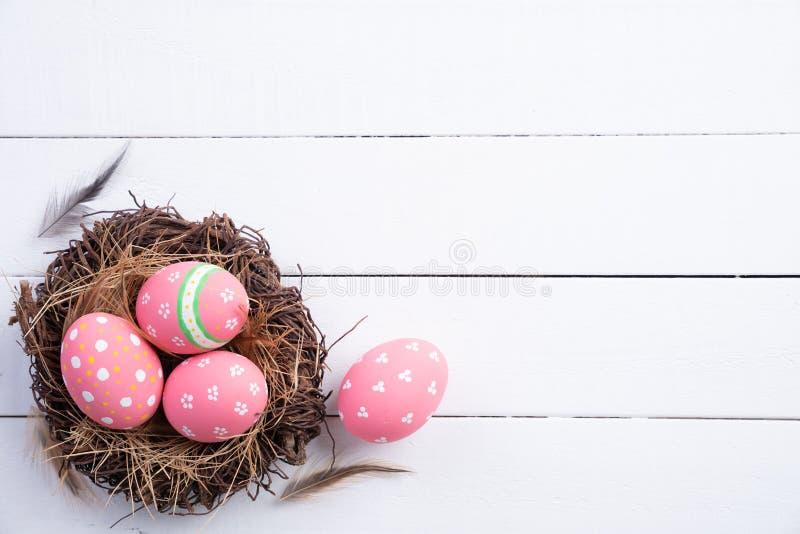 复活节快乐!五颜六色在巢与花和羽毛的复活节彩蛋在白色木背景 图库摄影