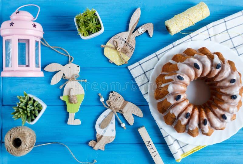 复活节快乐!在毛巾,鸡蛋,在蓝色木背景的木小兔的手工制造蛋糕 装饰复活节 免版税库存图片