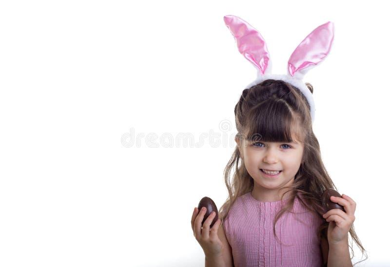 复活节快乐!有兔宝宝耳朵和朱古力蛋的儿童女孩 查出在白色 库存图片