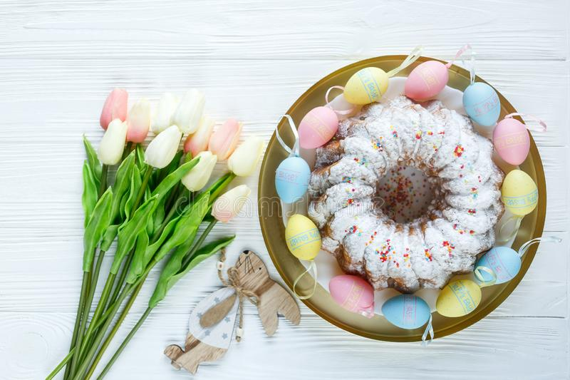 复活节快乐!有板材机智蛋糕和手画五颜六色的鸡蛋的,在白色木桌上的郁金香金黄盘子 关闭 装饰 免版税库存照片
