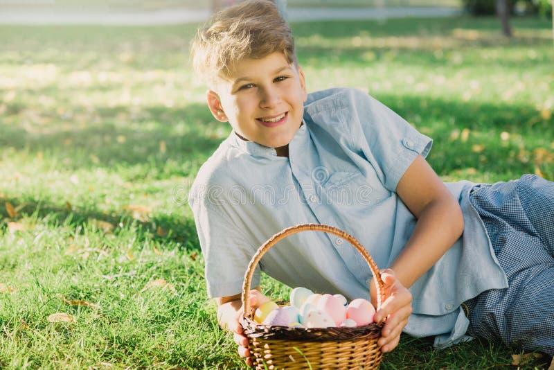 复活节快乐!蓝色衬衣的逗人喜爱的微笑的男孩少年在春天公园拿着篮子用在草的手工制造色的鸡蛋 装饰 库存照片