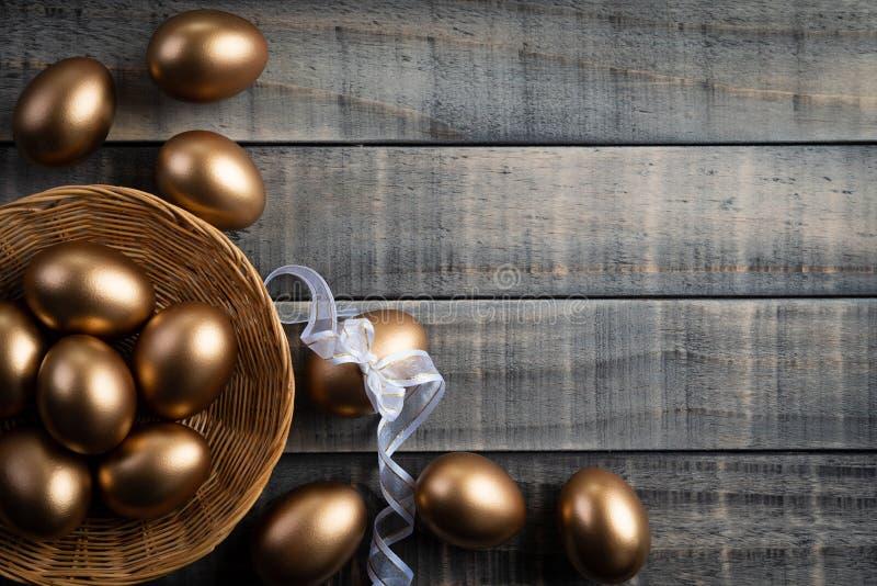 复活节快乐!金黄在巢和羽毛的复活节彩蛋在木背景 库存图片