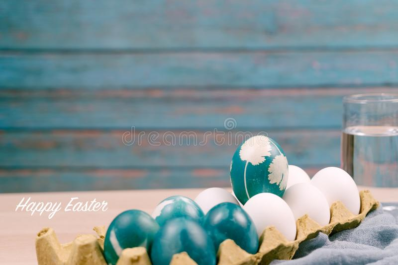 复活节快乐,站立在白色颜色鸡蛋的有机蓝色复活节彩蛋等待绘画,复活节假日装饰 库存照片