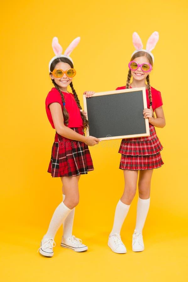 复活节来临 o 兔宝宝耳朵的小女孩有黑板的 公告的地方 学校项目 免版税库存照片