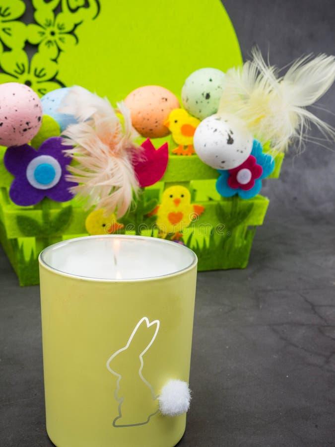 复活节构成、五颜六色的鸡蛋与羽毛,装饰花和黄色小鸡,燃烧的蜡烛用兔子 免版税图库摄影