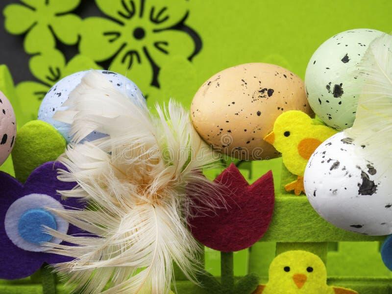 复活节构成、五颜六色的鸡蛋与羽毛,装饰花和黄色小鸡 免版税库存照片