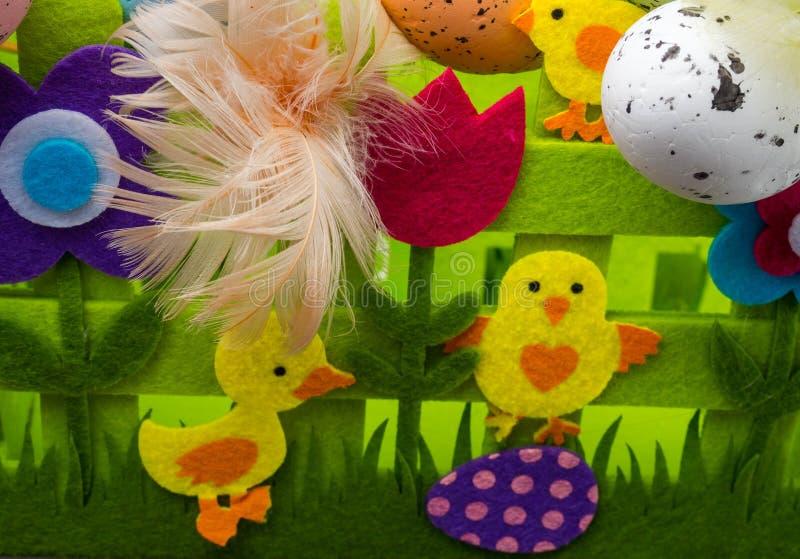 复活节构成、五颜六色的鸡蛋与羽毛,装饰花和黄色小鸡 库存照片