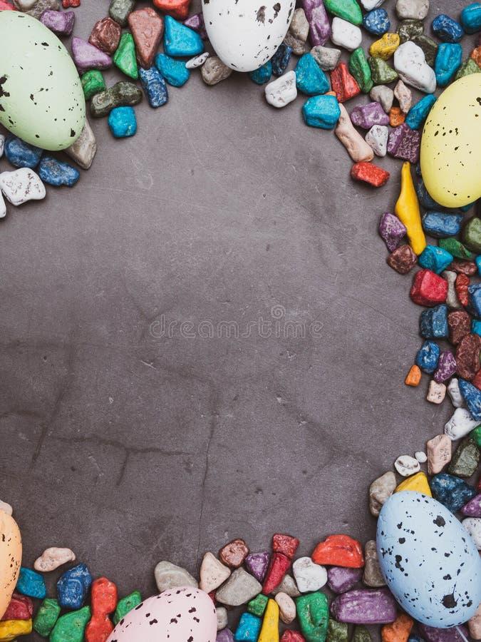 复活节构成用色的鸡蛋和甜点concreten背景,文本的空间 免版税库存照片