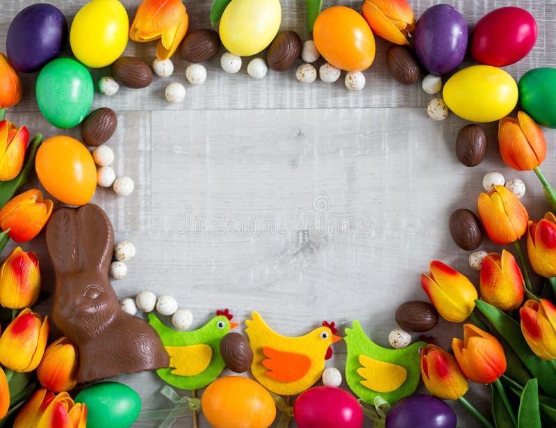 复活节框架背景-五颜六色的鸡蛋、装饰小鸡、郁金香、巧克力兔宝宝和甜点 库存图片