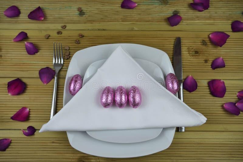 复活节桌在白色的餐位餐具用桃红色发光的被包裹的鸡蛋和紫色玫瑰花瓣和爱心脏装饰 库存照片
