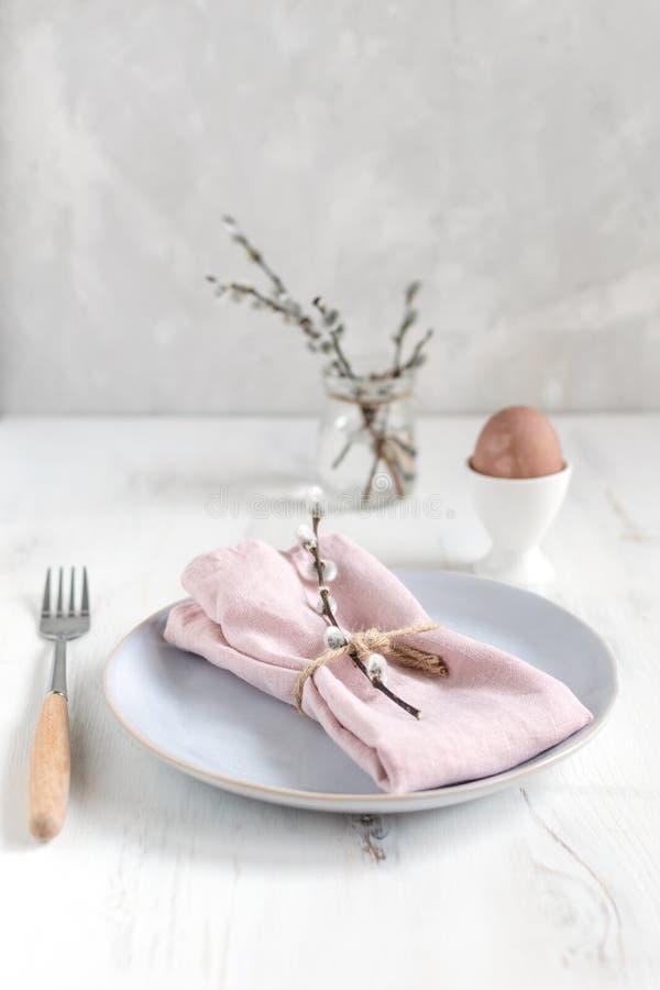 复活节桌设置想法,最小的装饰-桃红色餐巾,叉子,在白鸡蛋杯子,杨柳banch,白色木桌的色的鸡蛋 免版税库存图片