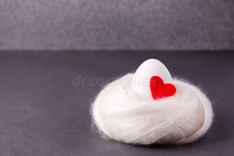 复活节概念、生活的起源,爱和纯净-与红色心脏的一个白鸡蛋在灰色的软的舒适温暖的巢在 库存照片