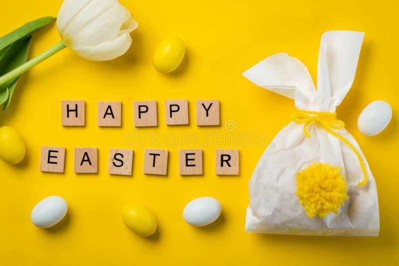 复活节概念-兔宝宝塑造了袋子用鸡蛋和花在明亮的黄色背景, 免版税库存照片