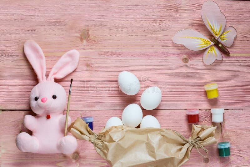 复活节欢乐集合用鸡蛋、花和复活节兔子,油漆,刷子,在土气木桌上的包装纸与copyspace 平的l 免版税库存照片