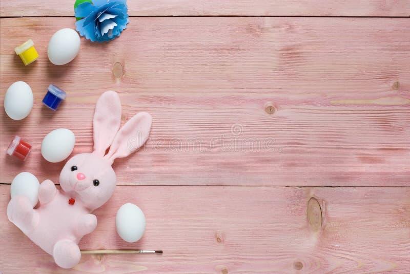 复活节欢乐集合用鸡蛋、花和复活节兔子,油漆,在土气木桌上的刷子与copyspace 平的位置,空间为mo 免版税图库摄影