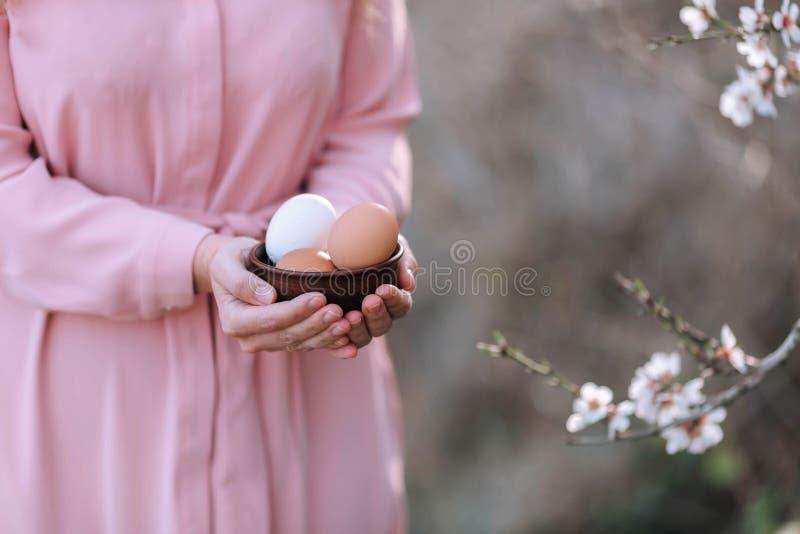 复活节的鸡蛋与春天花小树枝在女孩的手上 免版税库存照片