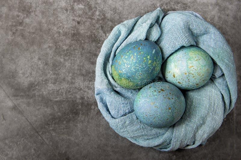 复活节绘了在巢形状滚动的毛巾的鸡蛋 在黑暗的大理石背景的青绿色树荫 免版税库存照片