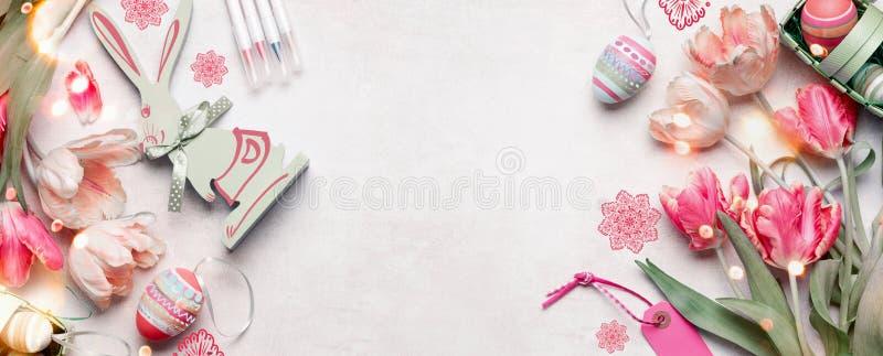 复活节背景横幅用复活节彩蛋和装饰辅助部件、郁金香花和滑稽的兔子在白色背景,顶面 免版税图库摄影