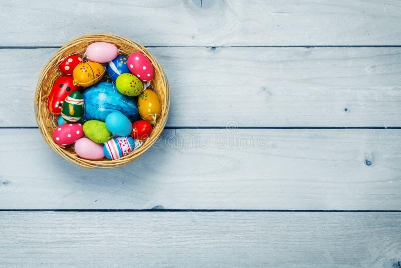 复活节背景,在篮子的复活节彩蛋在木头 免版税库存图片