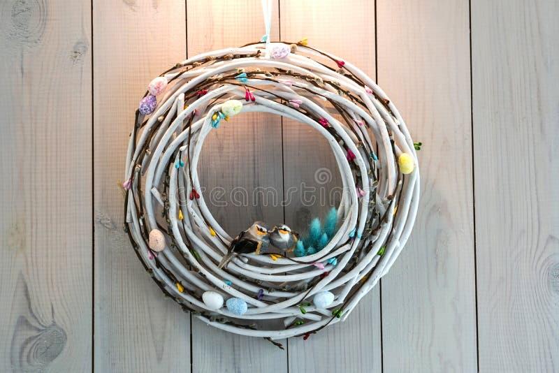 复活节花圈由枝杈鸡蛋和鸟做成在木墙壁背景 免版税库存照片