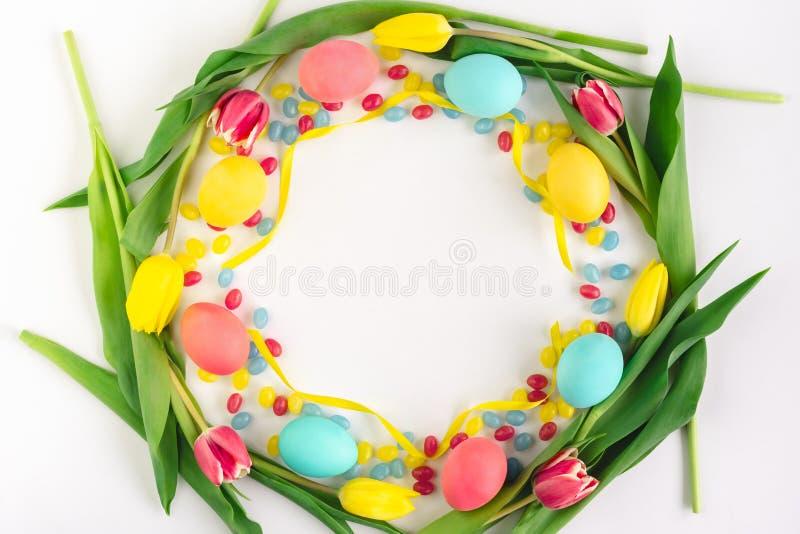 复活节花圈由黄色郁金香、五颜六色的鸡蛋和糖果制成在白色背景 平的位置 免版税库存图片