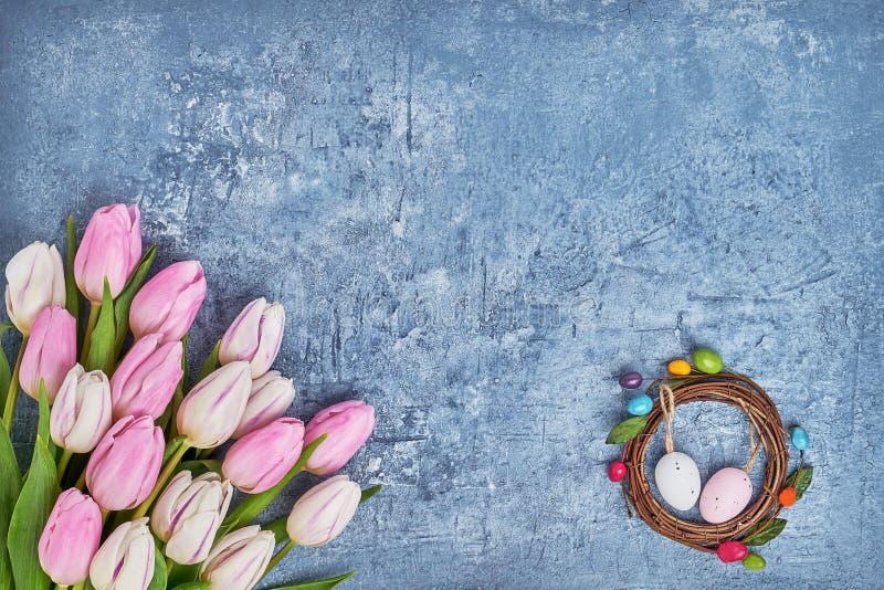 复活节花圈,白色和桃红色郁金香,在蓝色背景的装饰复活节彩蛋 顶视图 免版税图库摄影