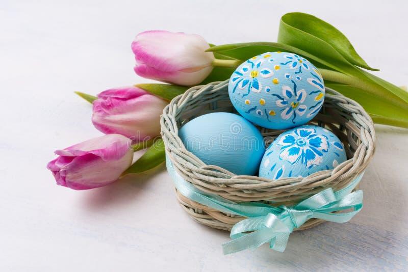 复活节蓝色绘了在thebasket和桃红色郁金香的鸡蛋 免版税库存照片