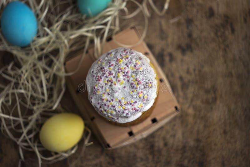 复活节蛋糕和五颜六色的复活节彩蛋在一张木桌上在wic 免版税图库摄影