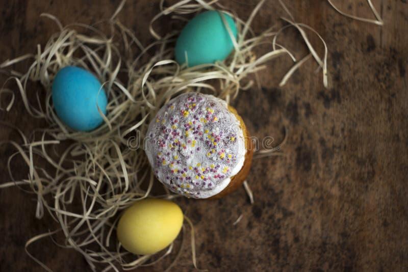 复活节蛋糕和五颜六色的复活节彩蛋在一张木桌上在wic 免版税库存照片