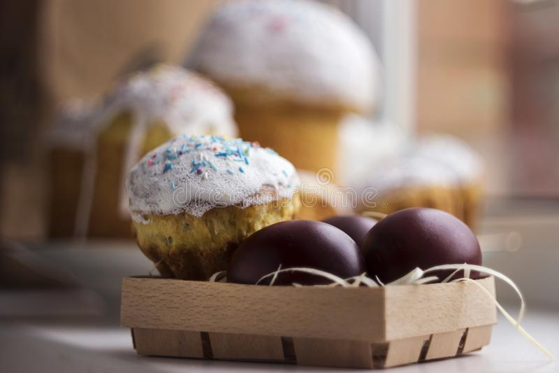 复活节蛋糕和五颜六色的复活节彩蛋在一张木桌上在wic 免版税库存图片
