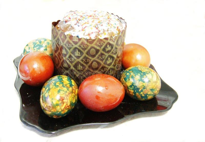 复活节蛋糕和五颜六色的被绘的鸡蛋在黑色的盘子 免版税库存图片