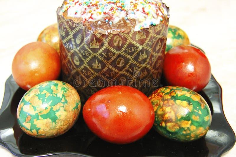 复活节蛋糕和五颜六色的被绘的鸡蛋在黑色的盘子 库存照片