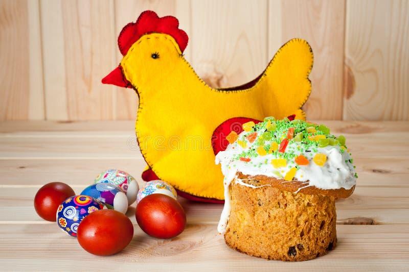 复活节蛋糕和被绘的鸡蛋与复活节鸡在一张木桌上 库存图片