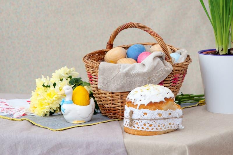 复活节蛋糕和bascket用色的鸡蛋和黄色花,在桌上 免版税库存照片