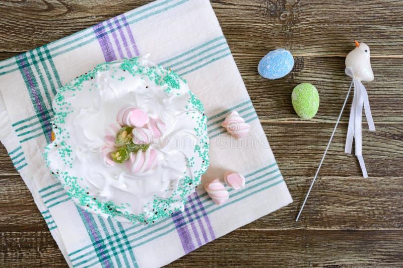 复活节蛋糕- kulich用干果子,装饰用在一张木桌上的蛋白甜饼 甜欢乐面包 免版税库存照片