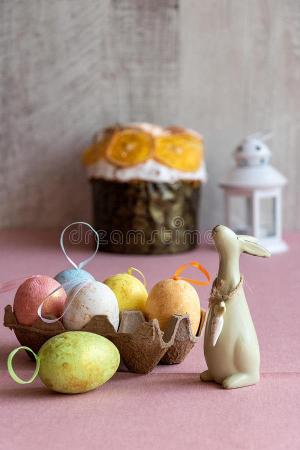 复活节装饰用五颜六色的鸡蛋、复活节蛋糕和一个淡色橄榄色的颜色兔宝宝 库存图片