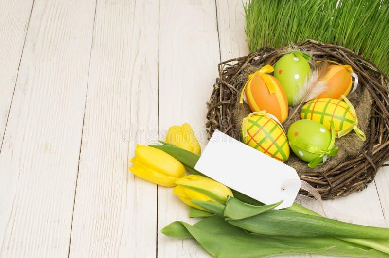 复活节装饰用鸡蛋和郁金香在木背景 免版税库存照片